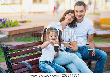 happy family kidding in the city sitting on a bench and eating ice cream