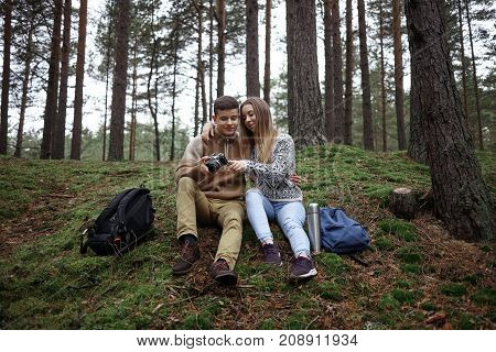Handsome guy and beautiful girl wearing sensible clothes watching pictures on professional camera sitting on grass close to each other among trees with backpacks and thermos bottle on the ground