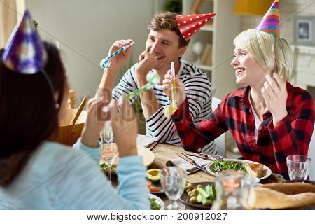 Group of happy young people wearing holiday caps celebrating Birthday with friends during party at home, focus on smiling couple