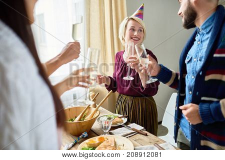 Group of happy young people wearing holiday caps celebrating Birthday with friends clinking champagne glasses during dinner party at home