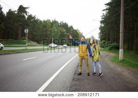 Couple of young hitchhikers man and woman in warm clothes standing at roadside showing gestures to car drivers by waving hands meaning they need a ride. People traveling hitchhiking and tourism
