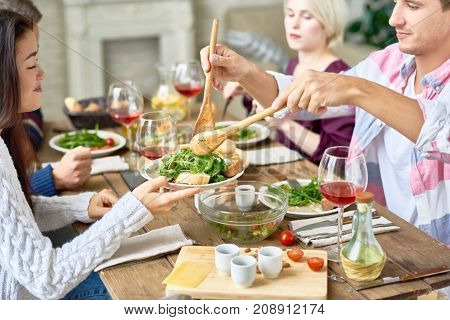 Portrait of four people eating at festive dinner table with delicious food at home, enjoying holiday celebration