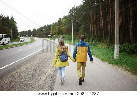 Rear view of male and female travelers dressed in warm clothes holding hands and walking along highway while hitchhiking together. People traveling active lifestyle and relationships concept