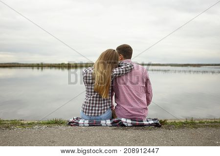 Rear view of romantic couple enjoying wild nature relaxing on plaid by the river. Young male and female sitting on grass by vast lake close to each other and admiring beautiful views around them