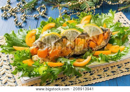 Mackerel baked with tomatoes and cheese served on lettuce with lemon and tomatoes decorated with parsley. Festive Christmas table setting: plate on lacy napkin glasses of wine on green background
