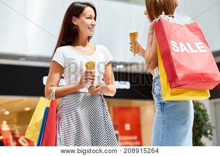 Portrait of two beautiful girls shopping in mall, chatting happily holding paper bags and eating ice cream cones