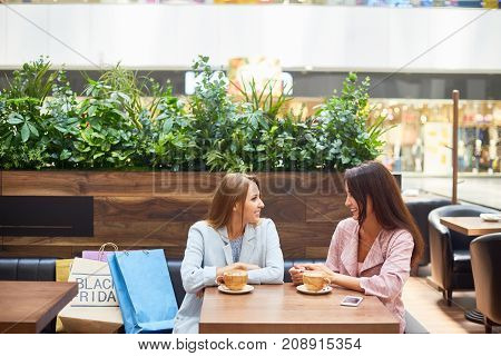 Portrait of two beautiful young women in shopping mall chatting and  drinking coffee at cafe table surrounded by paper bags on Black Friday
