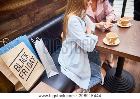High angle portrait of two beautiful young women in shopping mall chatting and  drinking coffee at cafe table surrounded by paper bags on Black Friday