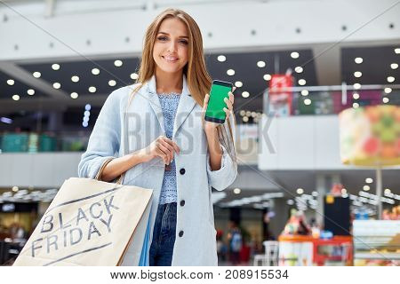 Portrait of beautiful young woman showing smartphone with blank green screen smiling happily to camera while shopping on Black Friday