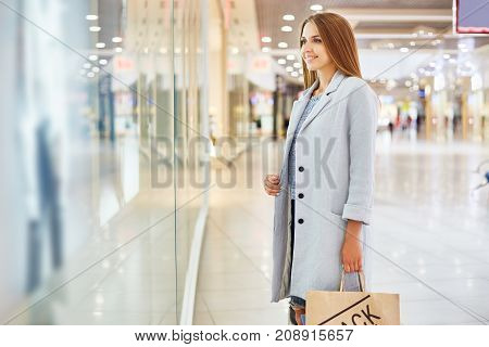 Portrait of beautiful young woman in shopping center looking at window displays of store and smiling, choosing clothes on Black Friday
