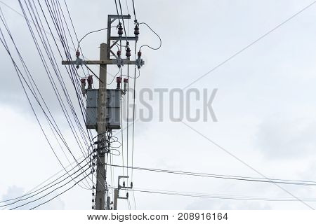 Energy and technology: electrical post by the road with power line cables transformers and phone lines against bright blue sky providing copy space.