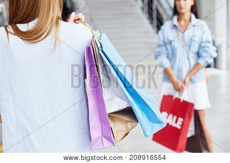 Portrait of two young women in shopping center both holding paper  bags with purchases during season sale, copy space
