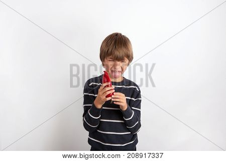 Young boy holding a sweet pepper expressing disgust and stretches out his tongue
