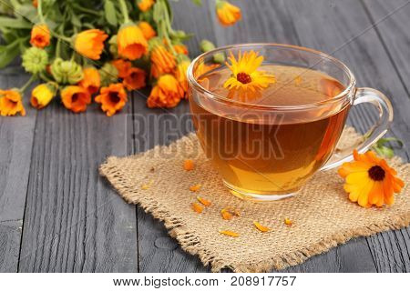 Calendula tea with fresh flowers on black wooden background.