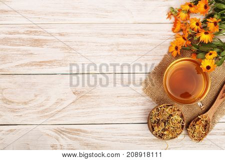 Calendula tea with fresh and dried flowers on white wooden background with copy space for your text. Top view.