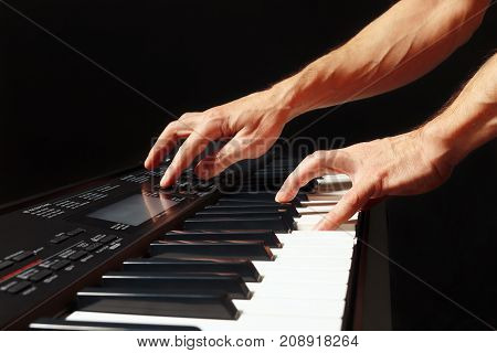 Hands of musician play the keys of the synth on a black background