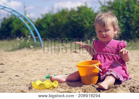 A little girl squints against bright sunlight. Adorable toddler girl in dress play with sand on sandbox.