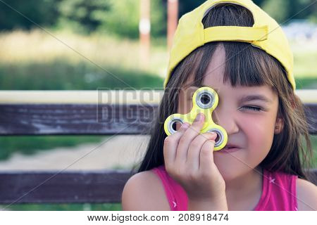 Little caucasian girl with Fidget Spinner held up to his eyes outdoors. Popular and trendy toy for children and adult.