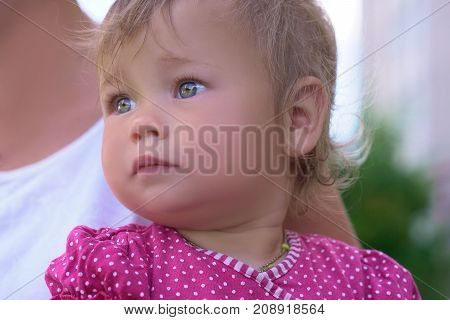 Portrait of pretty little girl on mother's hands. Family love concept.