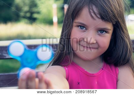 Young schoolgirl holding popular fidget spinner toy - close up portrait. Happy smiling child playing with Spinner.