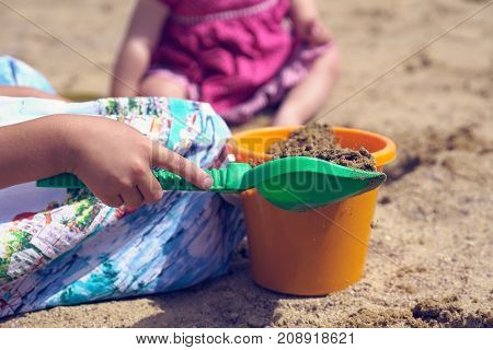Children's shovel and bucket close-up in the hands of a girl playing in the sandbox.