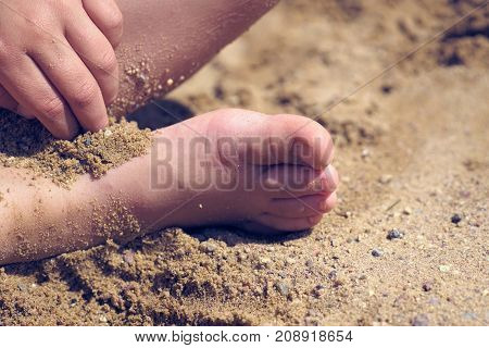 Close-up of children's feet in the sand on the beach or in the sandbox.