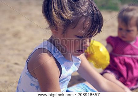 Two girls play in the sandbox on a hot summer day. Closeup portrait of the eldest girl in the foreground looking down.