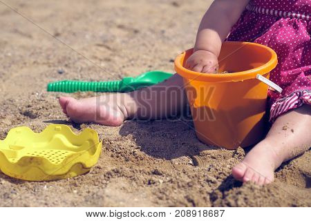 Close-up of the hand of a little girl playing with sand in the sandbox.