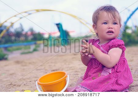 The little girl plays in a sandbox in a sunny day. Summertime children activities.