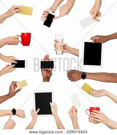 Set of male and female hands holding items. Gadgets, business crads and coffee cup in various hadns. Isolated at white background