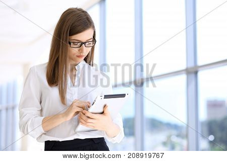 Modern business woman typing on laptop computer while standing in the office before meeting or presentation.