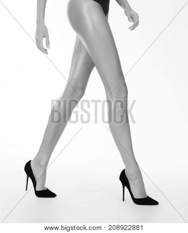 Walking girl in black high heels studio isolated monochrome shot