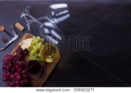 Red and wite wine in glasses with grape fruit, top view scene, copy space on wooden table