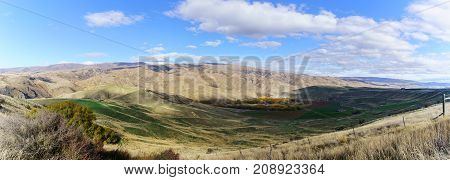 Panoramic image of Lindis Pass Scenic Reserve is the highest point on the South Island's state highway network of New Zealand offering mountain and tussock grassland scenery in Autumn