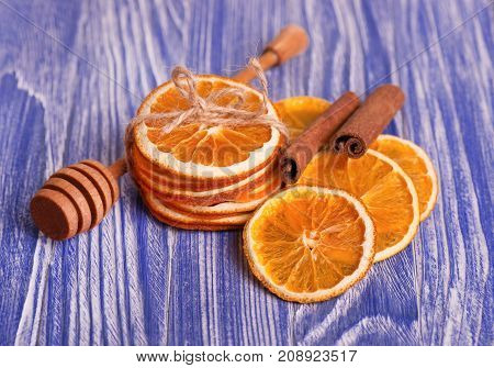 Dry slices of orange and cinnamon, on blue wooden background. Aromatic spices. Christmas decorations.