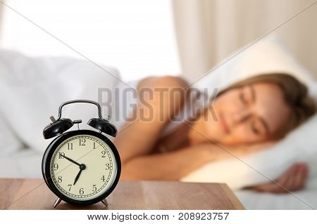 Beautiful young woman sleeping and smiling while lying in bed comfortably and blissfully on the background of alarm clock is going to ring. Sunbeam dawn on her face