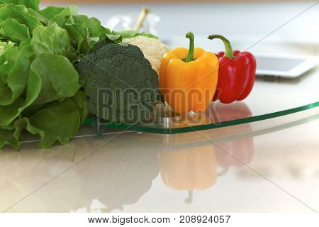 Kitchen interiors. Many vegetables and other meal at glass table are ready for been cooked soon.