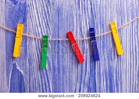Plastic colorful clothespins on blue wooden background