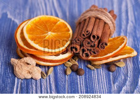 Dry slices of orange, cinnamon, ginger and cardamom, on blue wooden background. Aromatic spices. Christmas decorations.