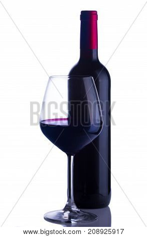 High glass with still red wine and wine bottle isolated on white background