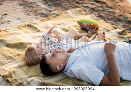 father with a little daughter lie on a blanket on sand