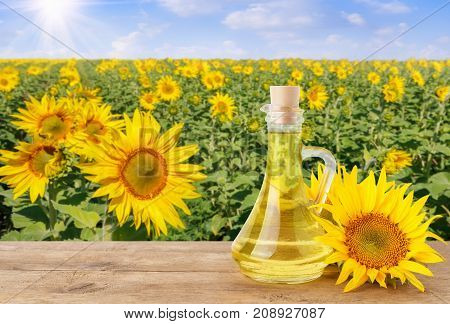 sunflower oil in glass bottle and fresh sunflowers on wooden table with natural background. Blooming sunflower field with blue sky and sun. Agriculture and harvest concept