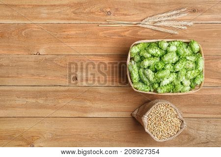 fresh green hops in basket and barley grains in bag on wooden table with copy space top view. Hop cones for beer. Ingredients for brewing