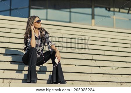 Brunette Woman Sitting On Stairs  While Listning Music And Using Smartphone