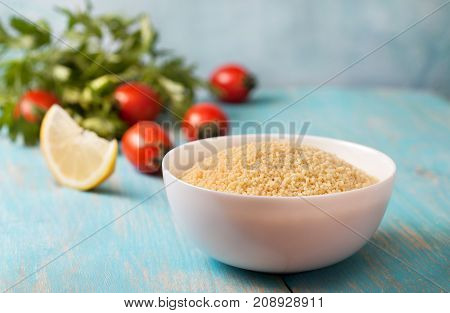 couscous and fresh vegetables: tomatoes lemon parsley on a blue background.