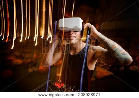 DJ in virtual reality glasses dressed in black shirt and with tattoo plays the track in club