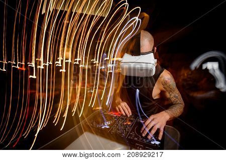 DJ in virtual reality glasses dressed in black shirt and with tattoo turns the records in night club