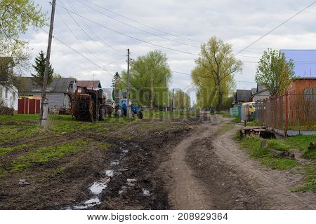 6 May 2017: Photo of village street with a tractor and dirt road. Kivsert-Yanishevo. Russia.