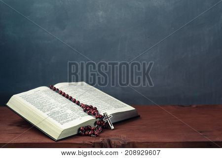 Bible and a crucifix on an old table. Beautiful background.Religion concept.
