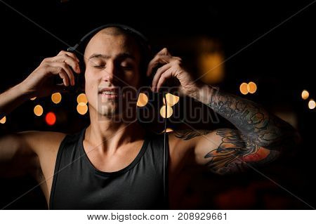 Handsome tattooed DJ in headphones on the background of night club lights with closed eyes
